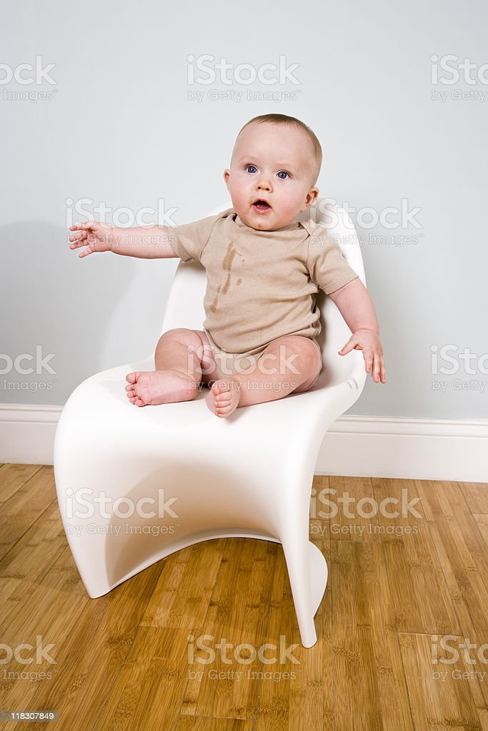 Baby watching from a chair stock photo
