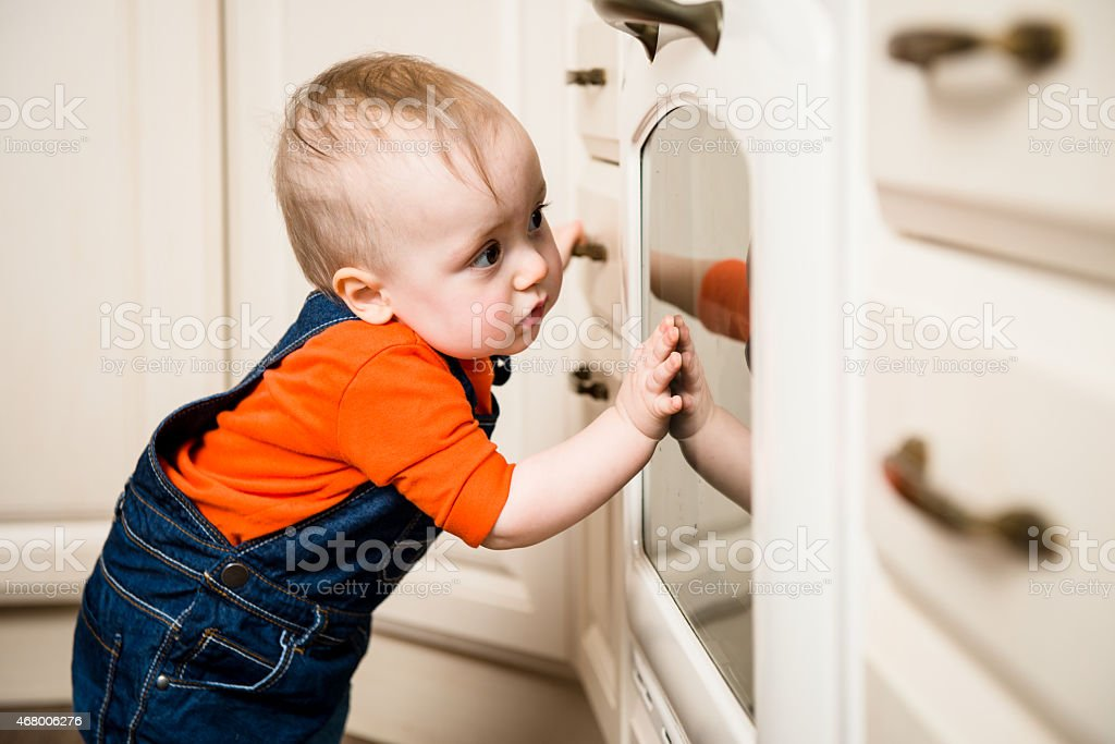 Baby watching inside kitchen oven stock photo