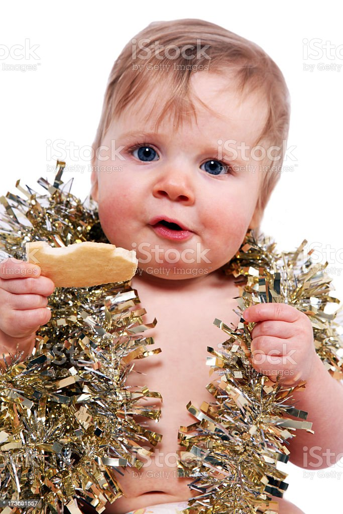 Baby Wearing Christmas Ornaments and Eating Cookie royalty-free stock photo