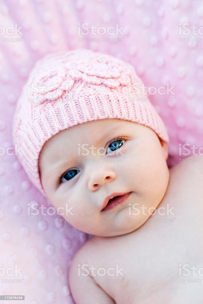 Baby wearing pink beanie lying on pink blanket royalty-free stock photo
