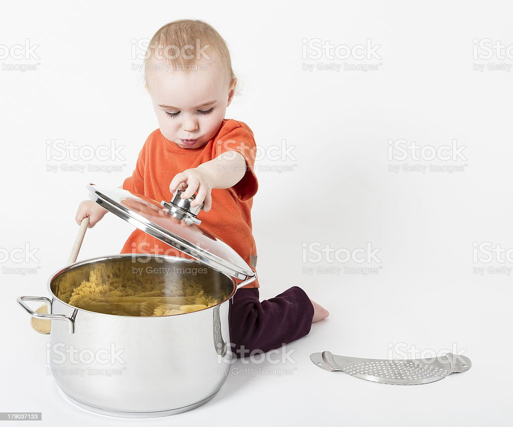 baby with big cooking pot stock photo