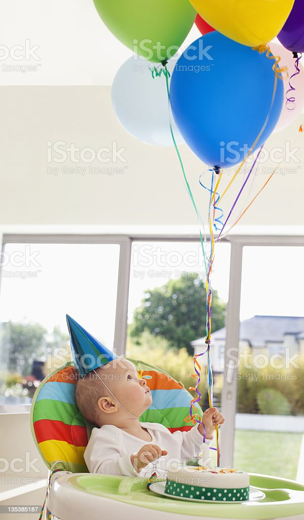 Baby with birthday cake holding balloons royalty-free stock photo