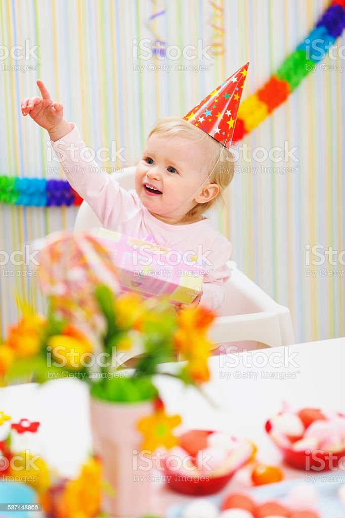 baby with birthday gift pointing in corner stock photo