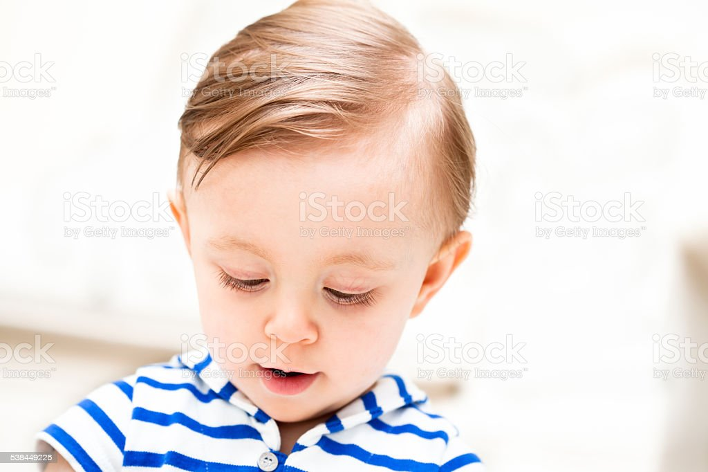 Baby with blue striped shirt looking down stock photo