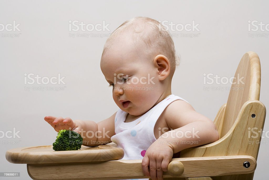 Baby with broccoli stock photo