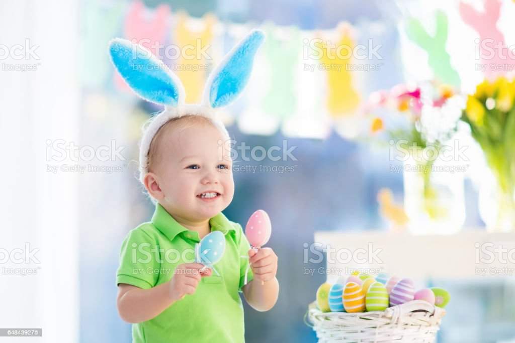 Baby with bunny ears on Easter egg hunt stock photo