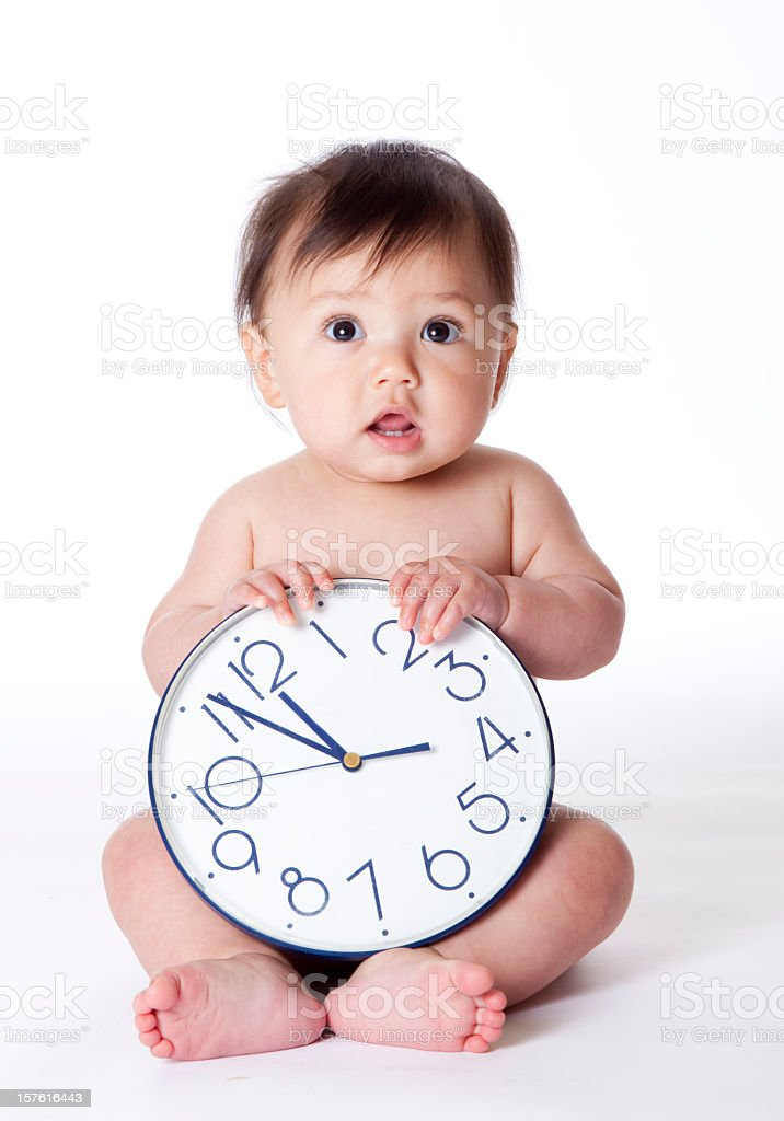 Baby with clock on its lap on a white background stock photo