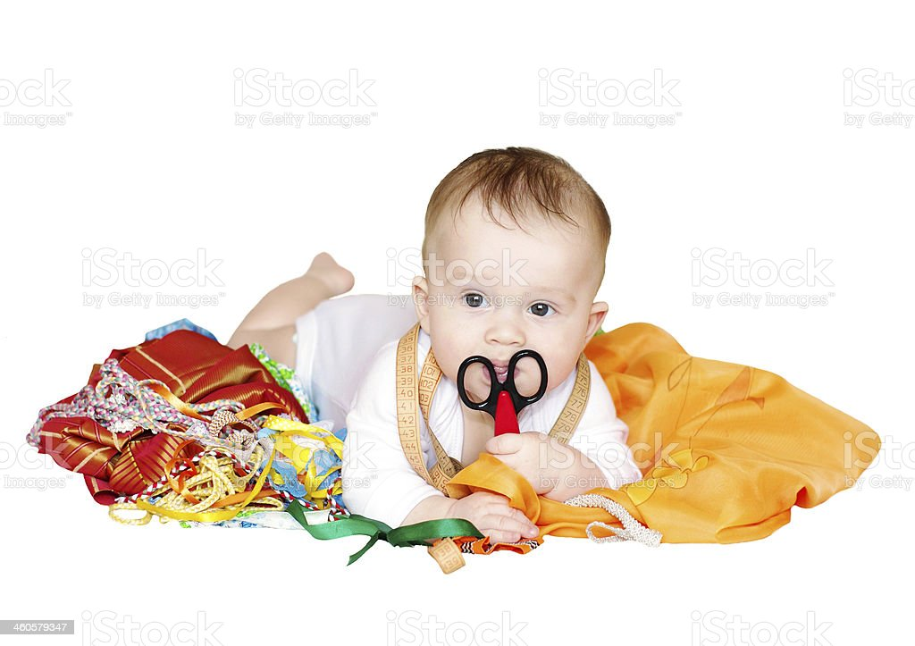 baby with fabrics, ribbons and scissor on white background stock photo
