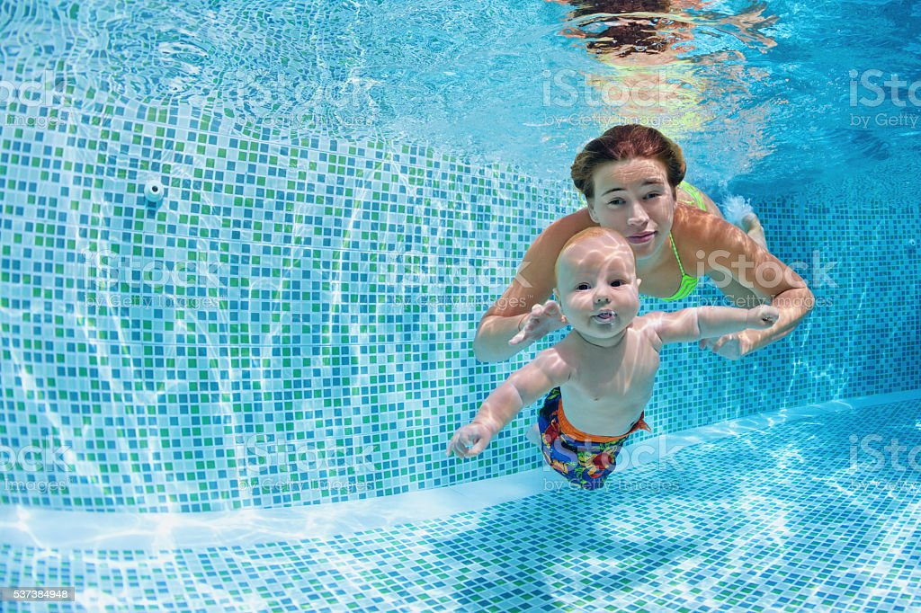 Baby with mother learn to swim underwater in swimming pool stock photo