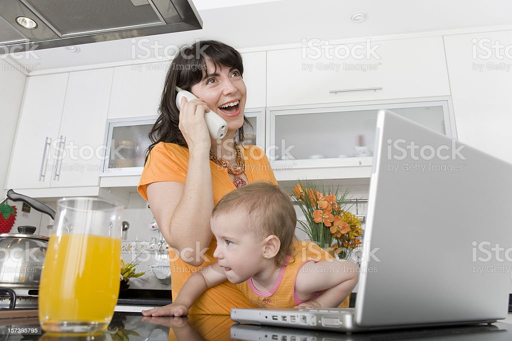 Baby with mother talking on the phone and laptop royalty-free stock photo