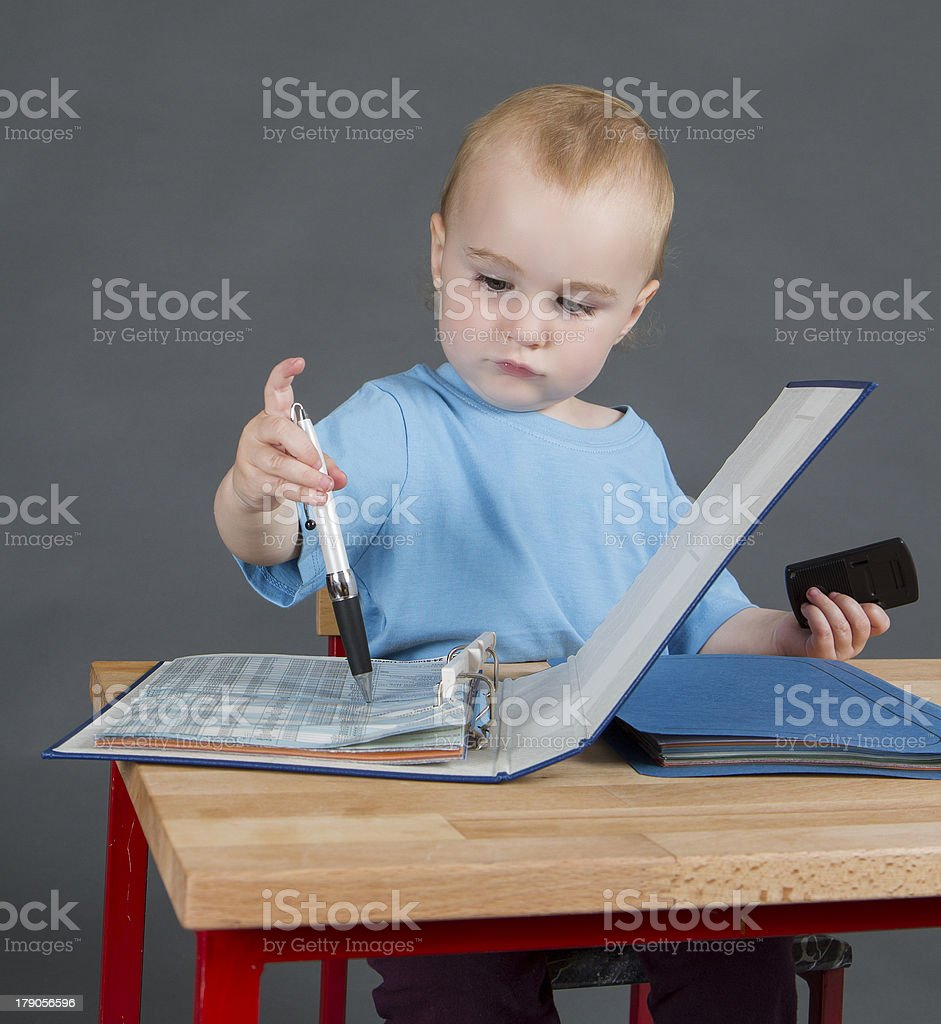 baby with paperwork at wooden desk stock photo