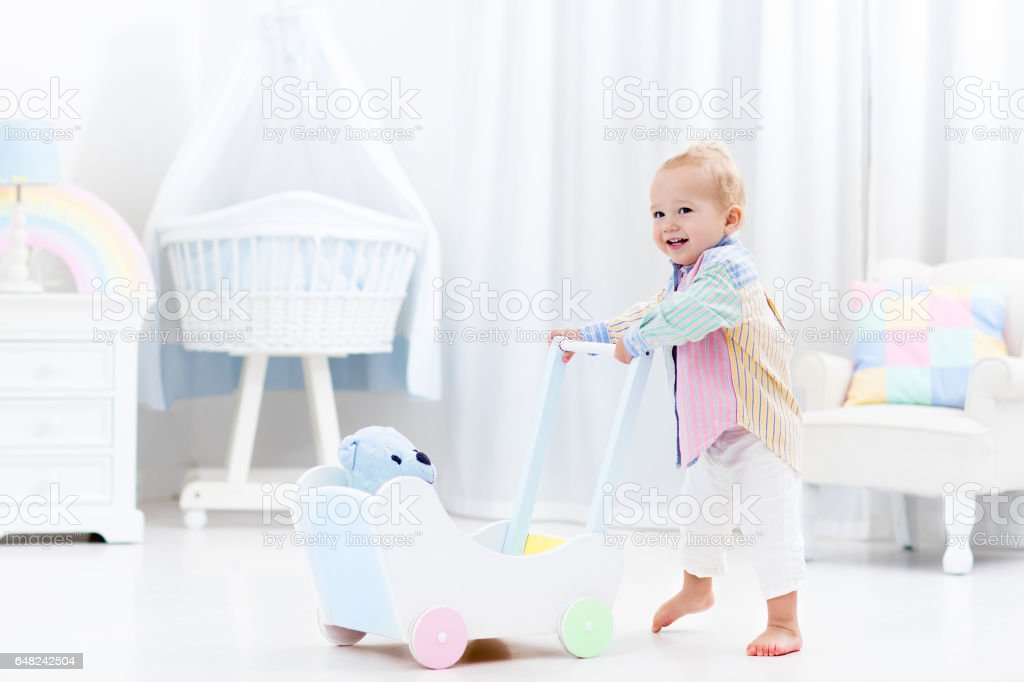 Baby with push walker in white bedroom stock photo