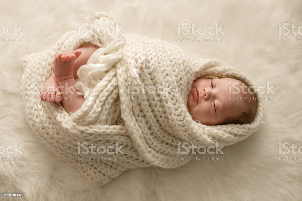 Baby wrapped in a blanket stock photo