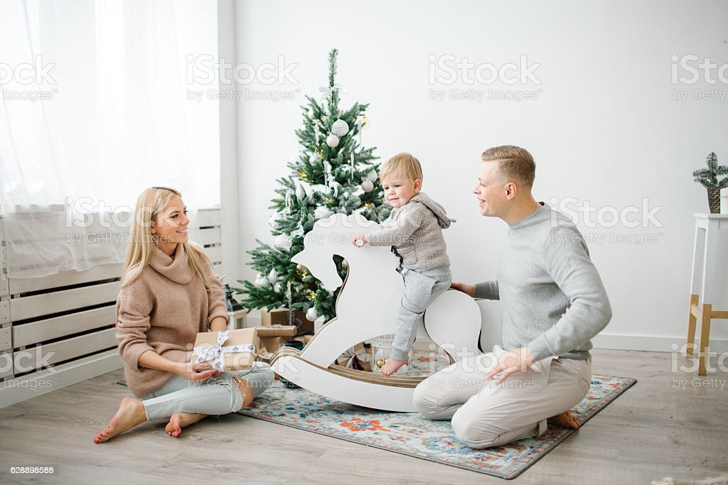 Baby-boy on horse swing near christmas decorated tree with paren stock photo