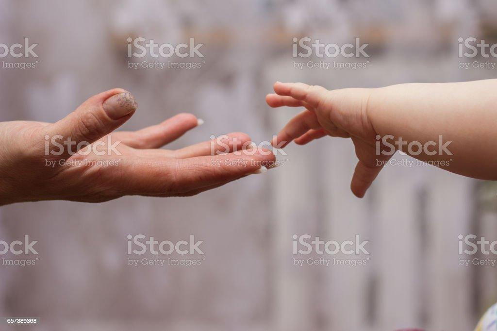 baby's hand reaching up to its stock photo