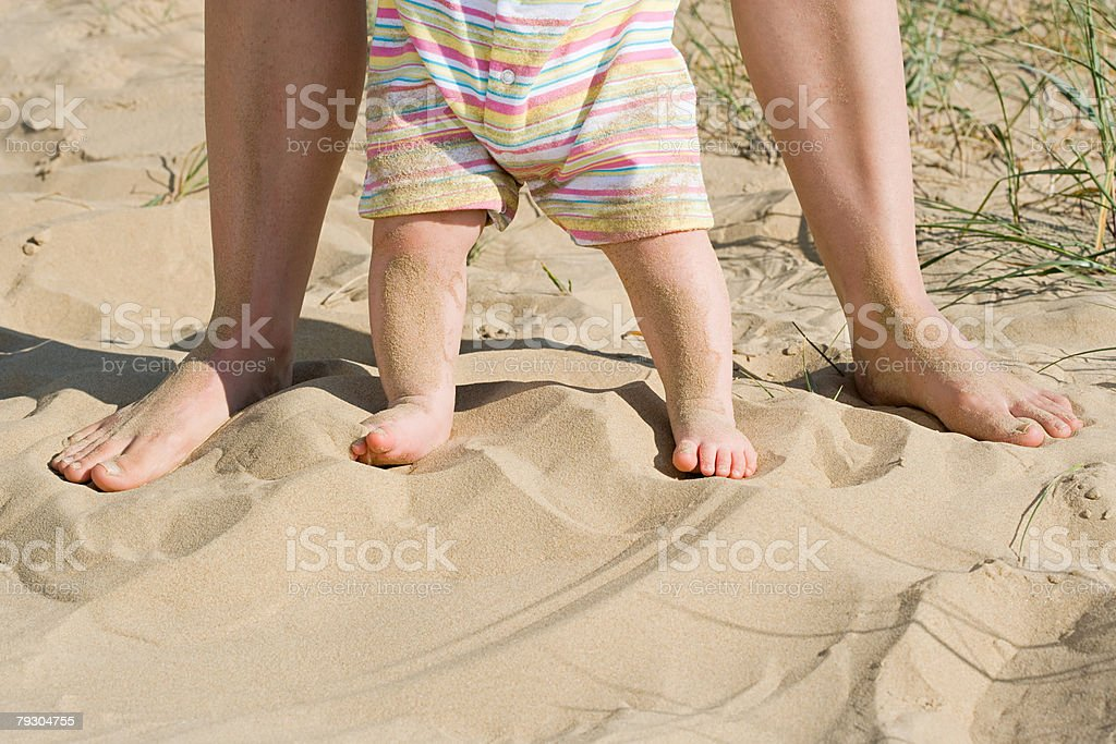 A babys legs and an adults legs stock photo