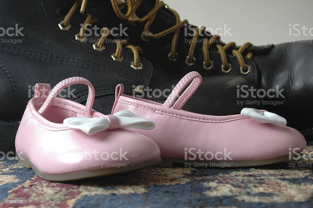 Baby's pink shoes next to daddy's big black boots. stock photo