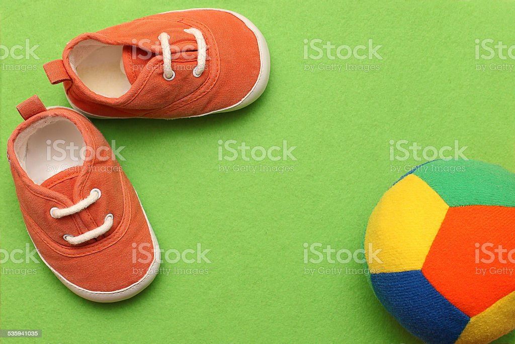 Baby's sneakers with color ball on green background stock photo
