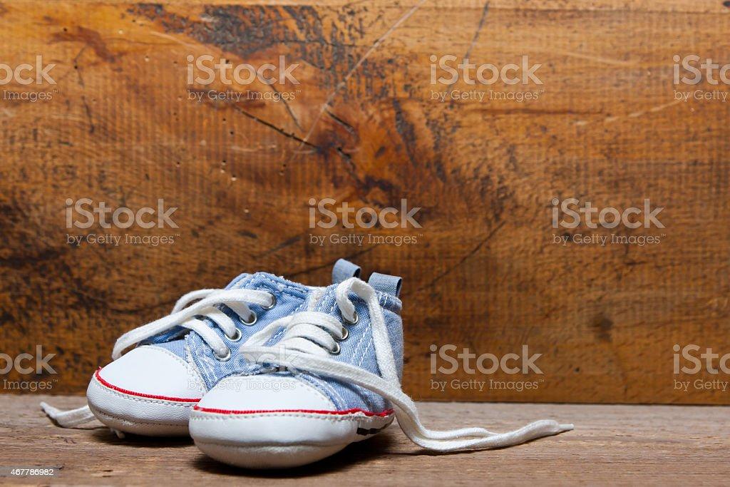 Babyschuhe vor einer Holzwand stock photo