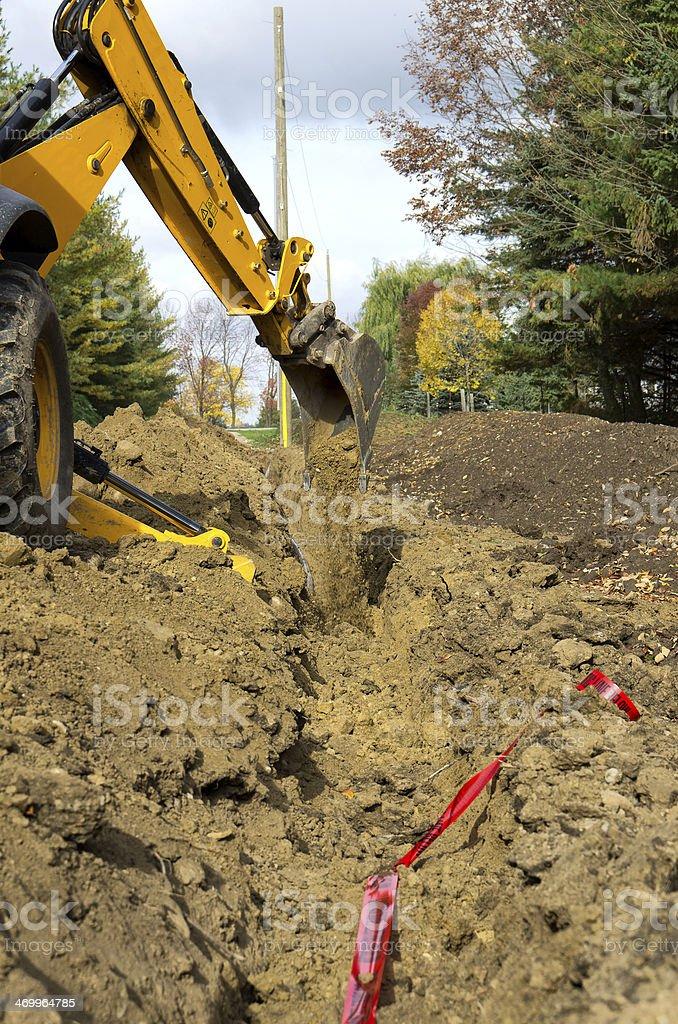 Bachoe Burying Power Line stock photo