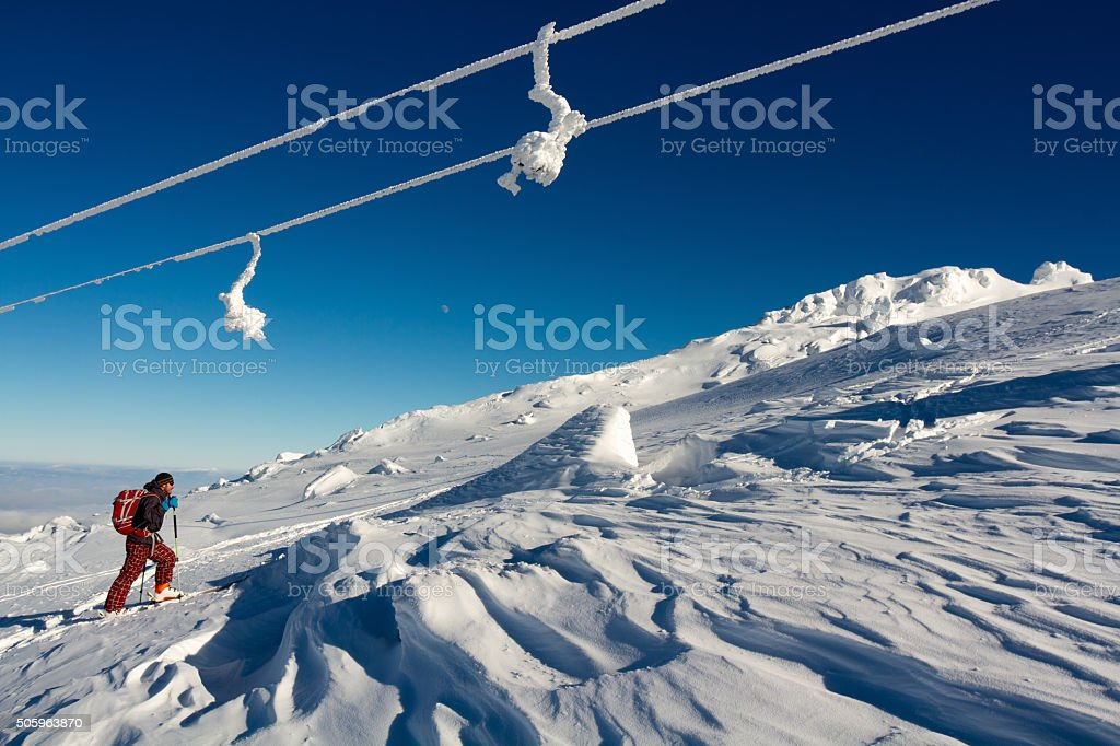 Back country skier climbing a slope covered by powder snow stock photo