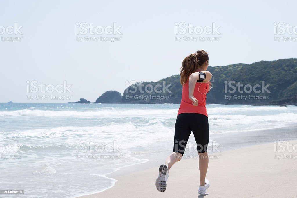 Back figure of a woman running on beach for diet stock photo