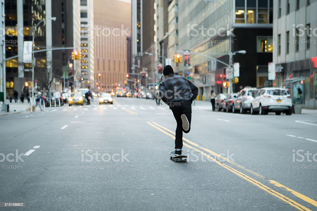 Back figure of young skateboarder cruising donw the city street stock photo