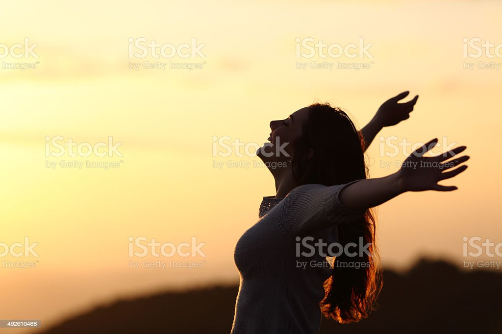 Back light of a woman breathing raising arms stock photo