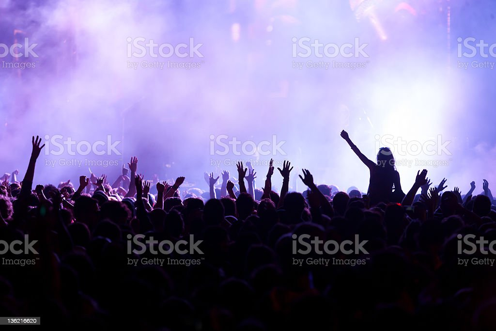 A back lit crowd with arms up at a music concert with a woman on a...