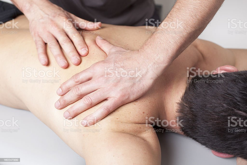 Back massage given to a young man stock photo