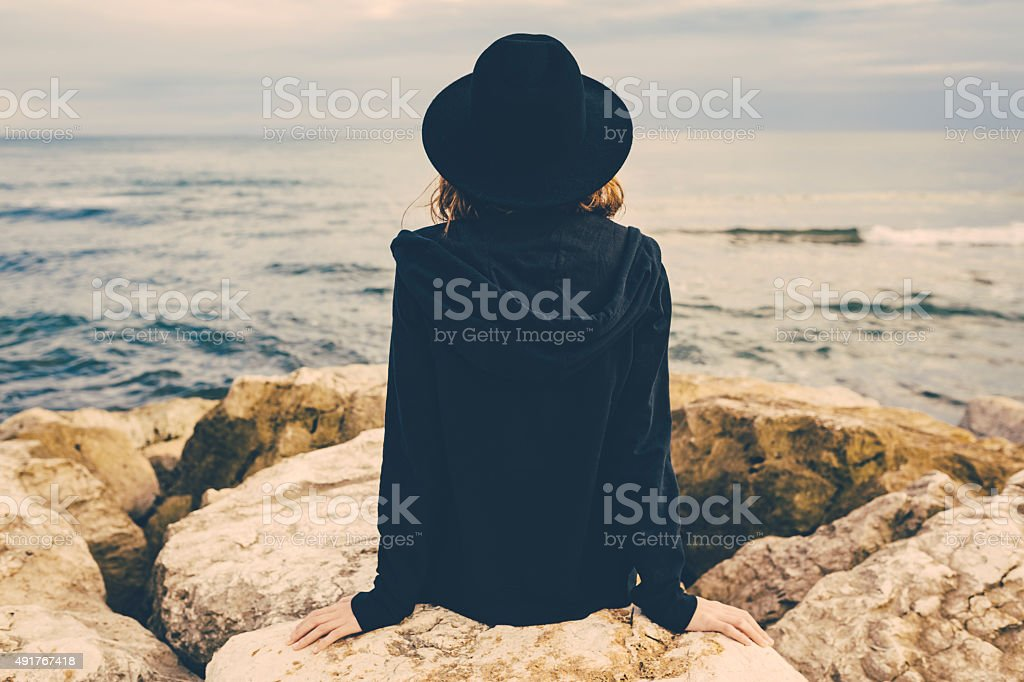 Back of a girl sitting on a pier stock photo