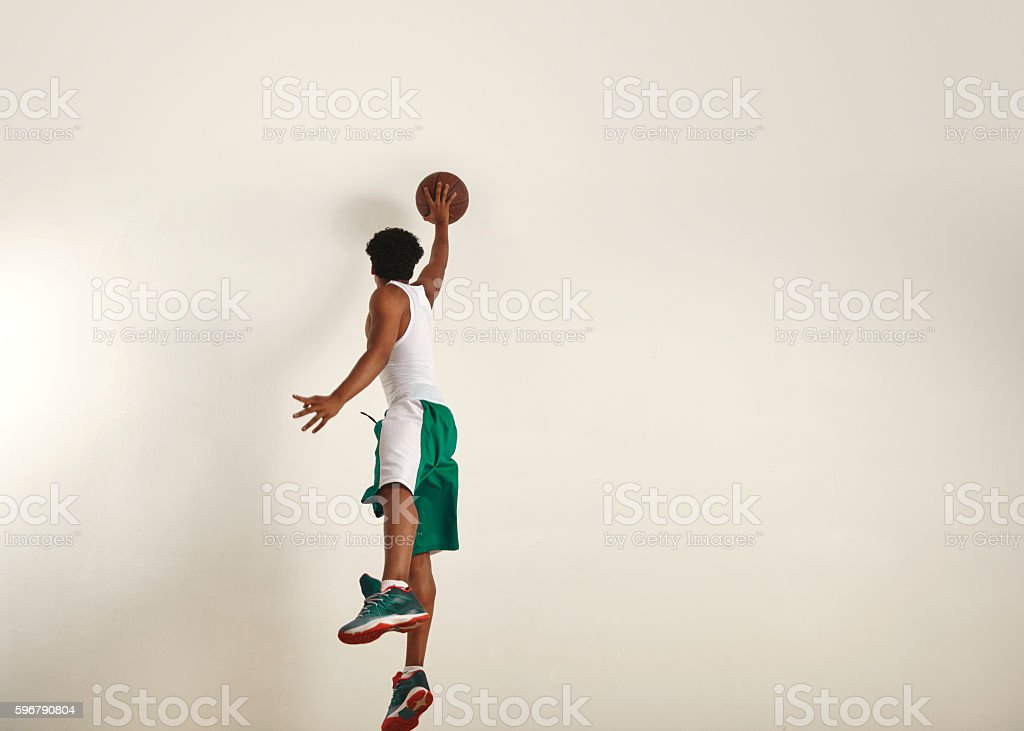 Back of a jumping basketball player shooting  ball stock photo