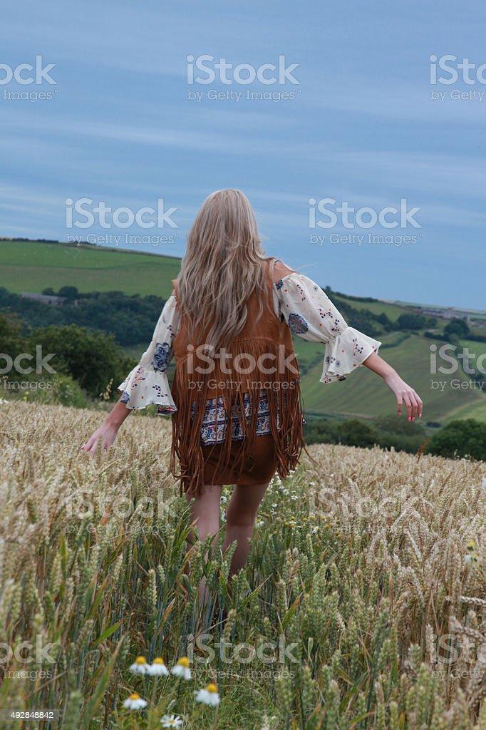 Back of a teenage girl walking in a wheat field stock photo