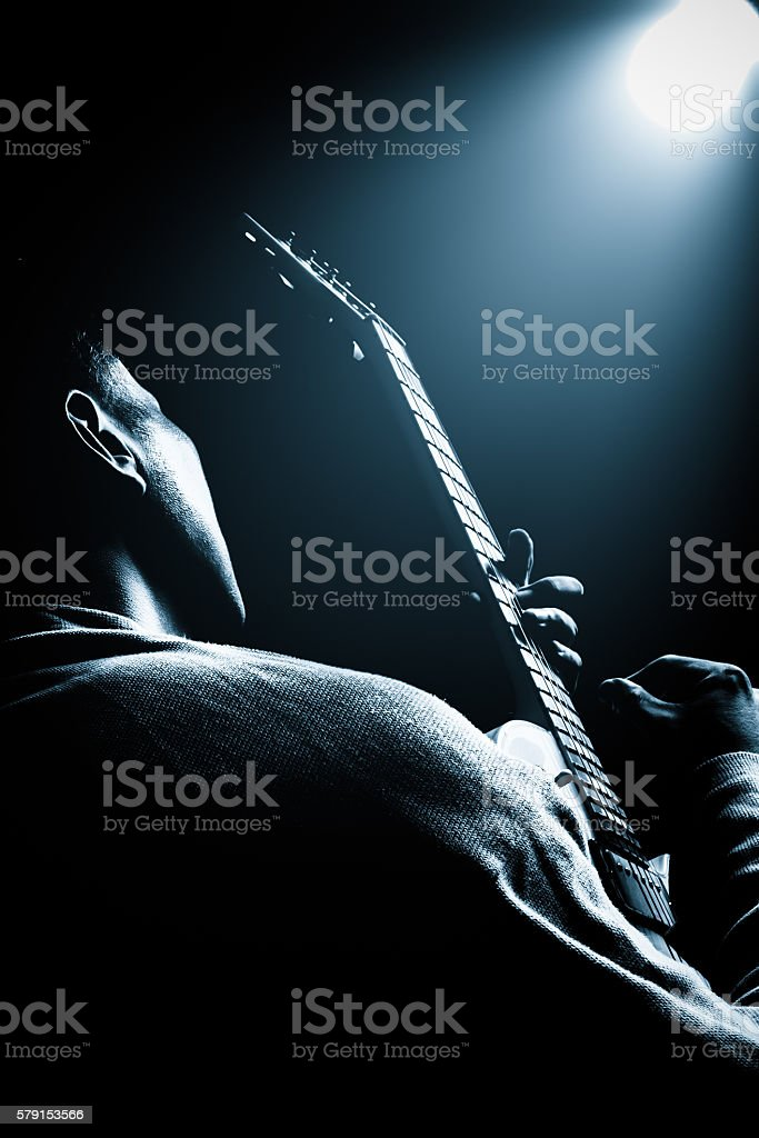 back of asian musician playing electric guitar with spotlight stock photo