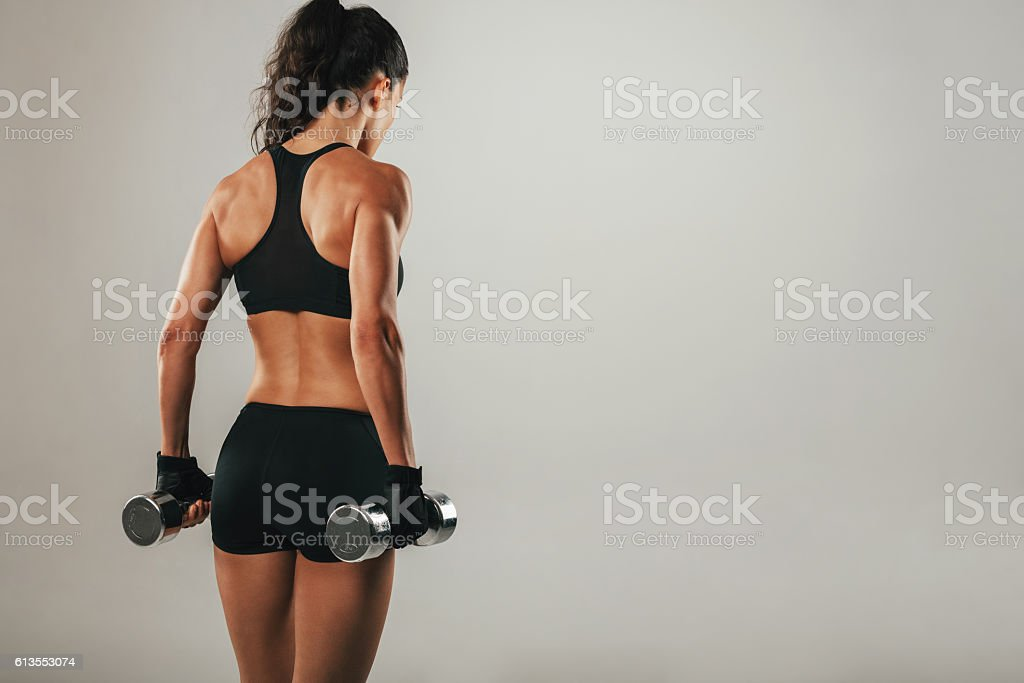 Back of athletic woman holding weights stock photo