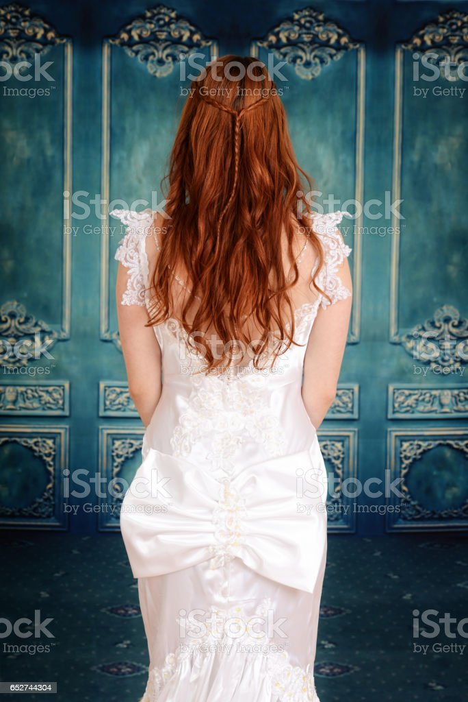 back of bride and a blue wood wall stock photo