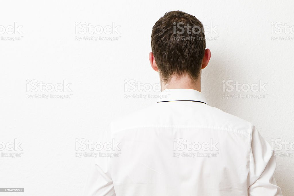 Back of Businessman against a Wall. stock photo