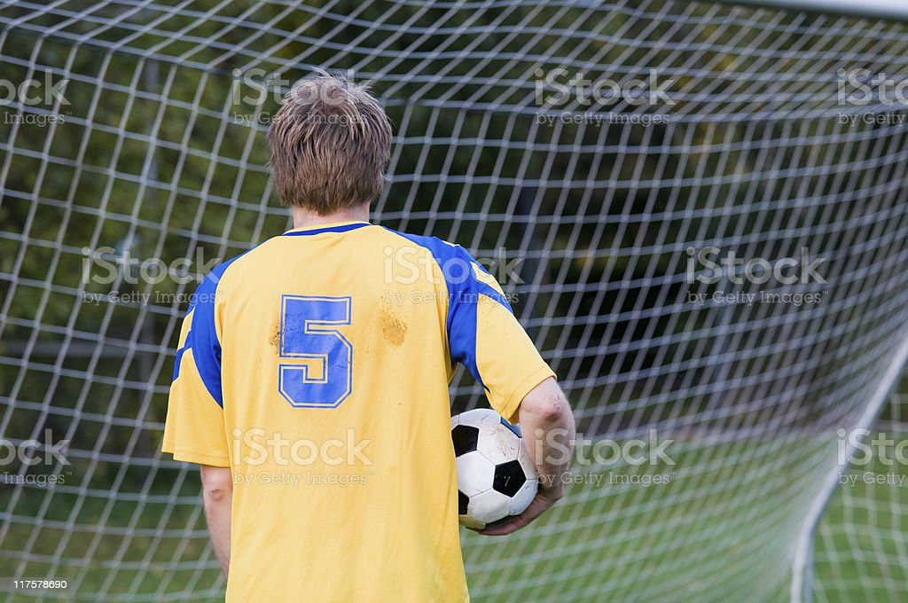 Back of soccer player standing in a goal royalty-free stock photo