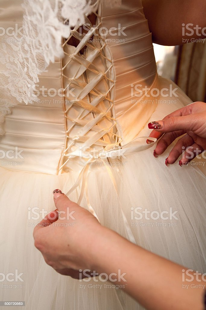 back of the wedding dress and hands stock photo