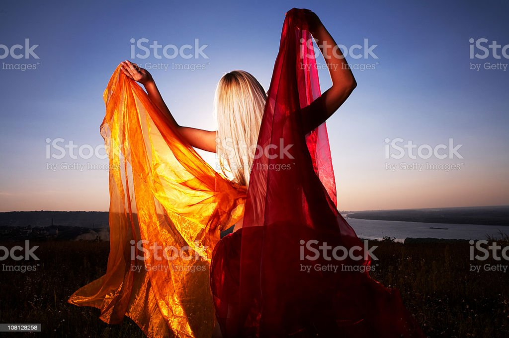Back of Woman Holding Red and Orange Silk at Sunset royalty-free stock photo