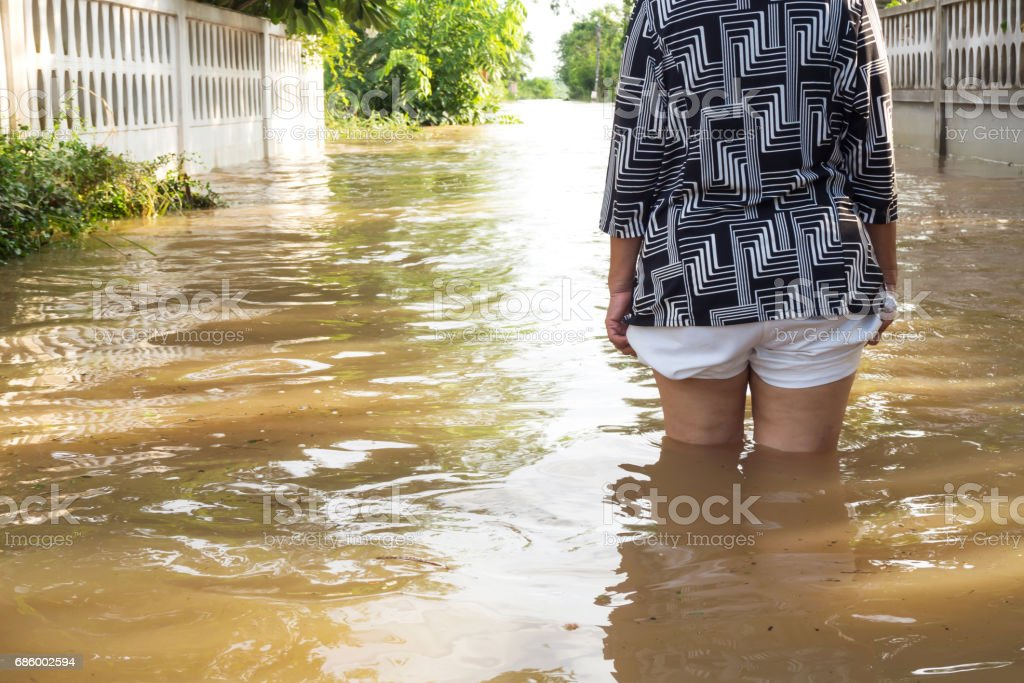 Back of woman standing in Flood. Flooding in house. Closeup on her leg. stock photo