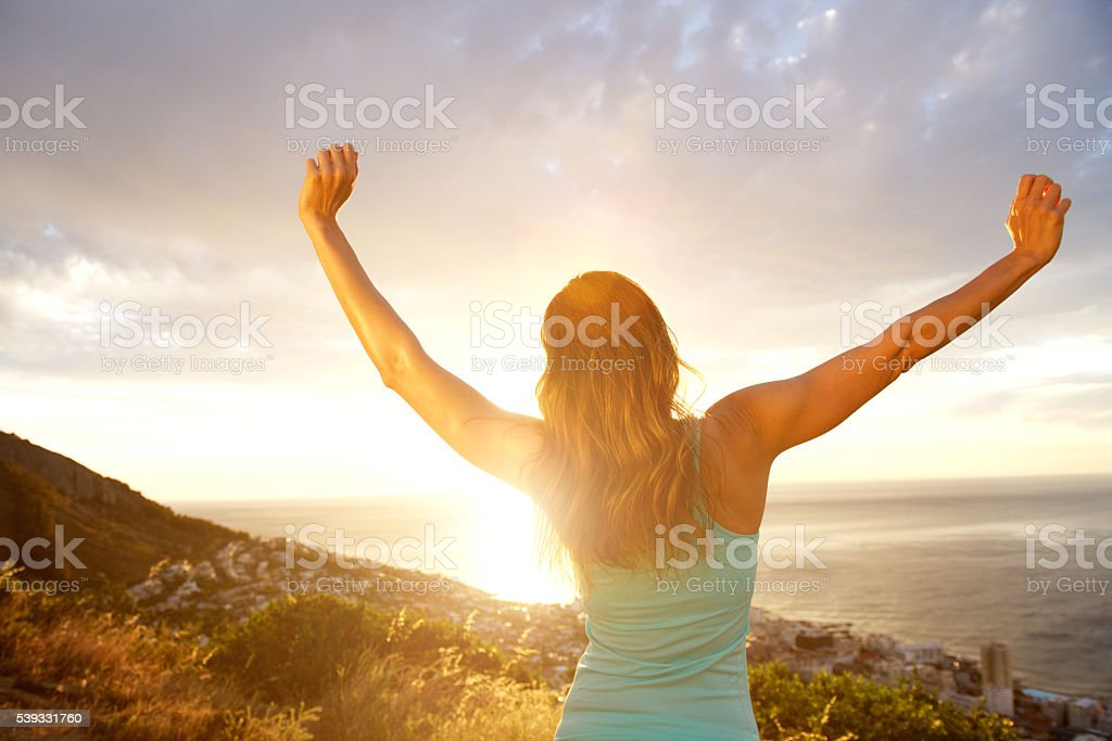 Back of woman with arms outstretched during sunset stock photo