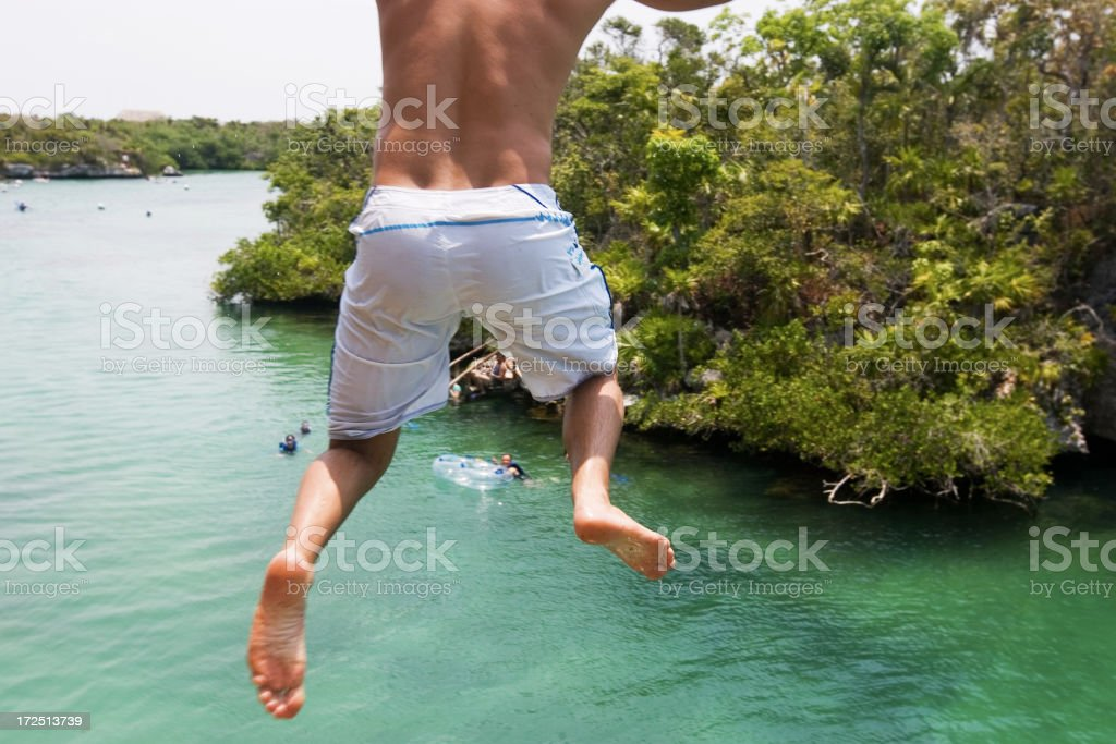 Back of Young Man Jumping off Cliff into River, Copyspace royalty-free stock photo