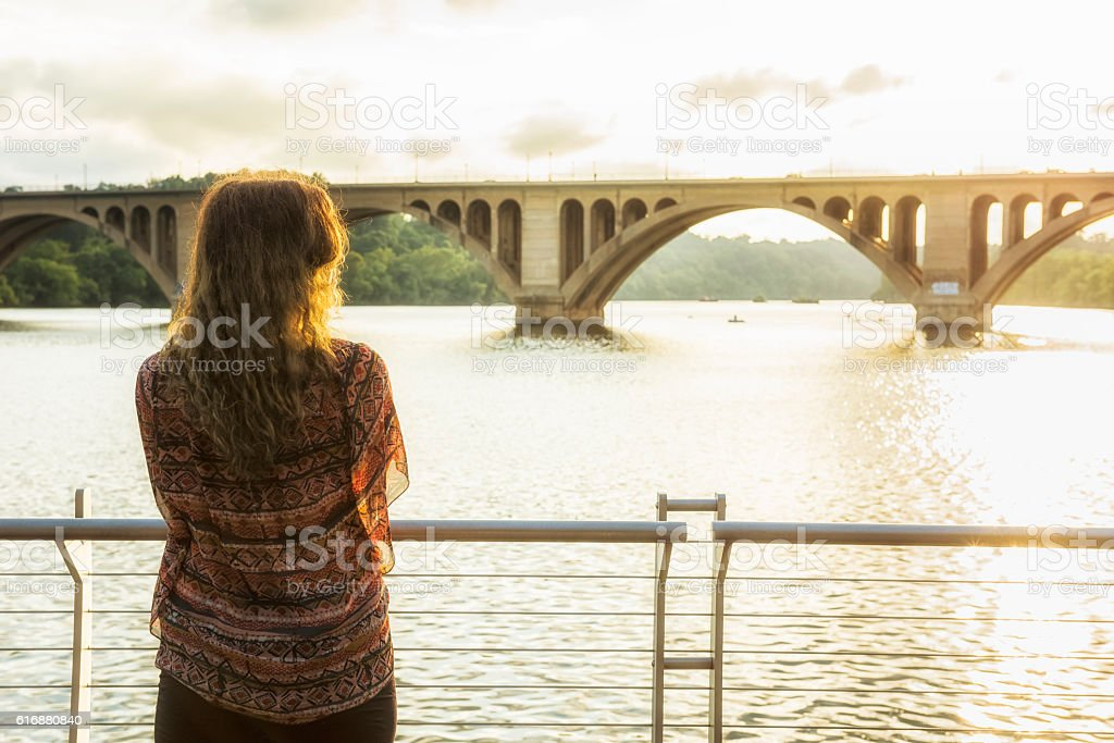 Back of young woman looking over potomac river stock photo