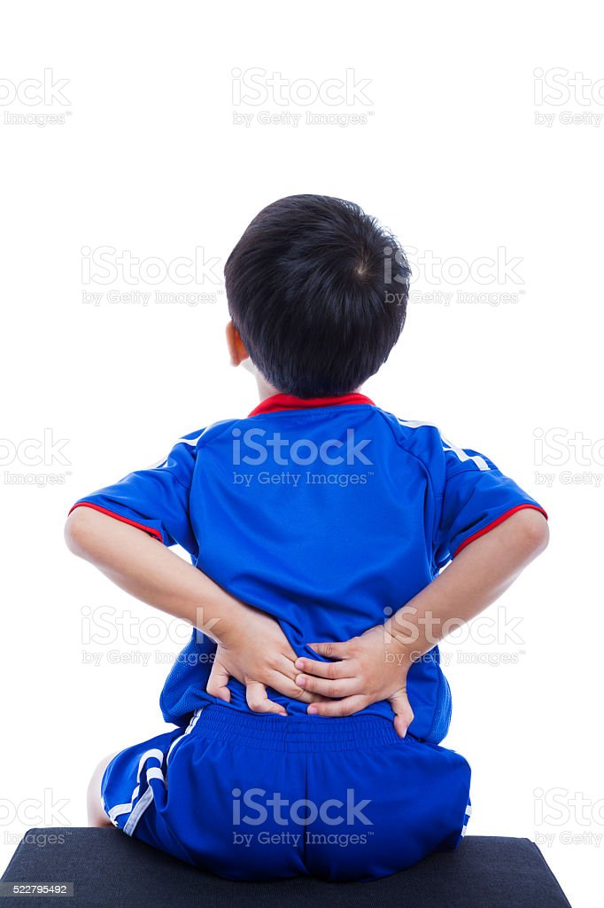 Back pain. Child rubbing the muscles of his lower back stock photo