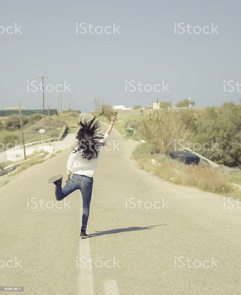 Back portrait of single young girl jumping in the road royalty-free stock photo