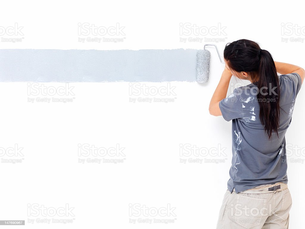 Back side view of a woman painting the wall stock photo