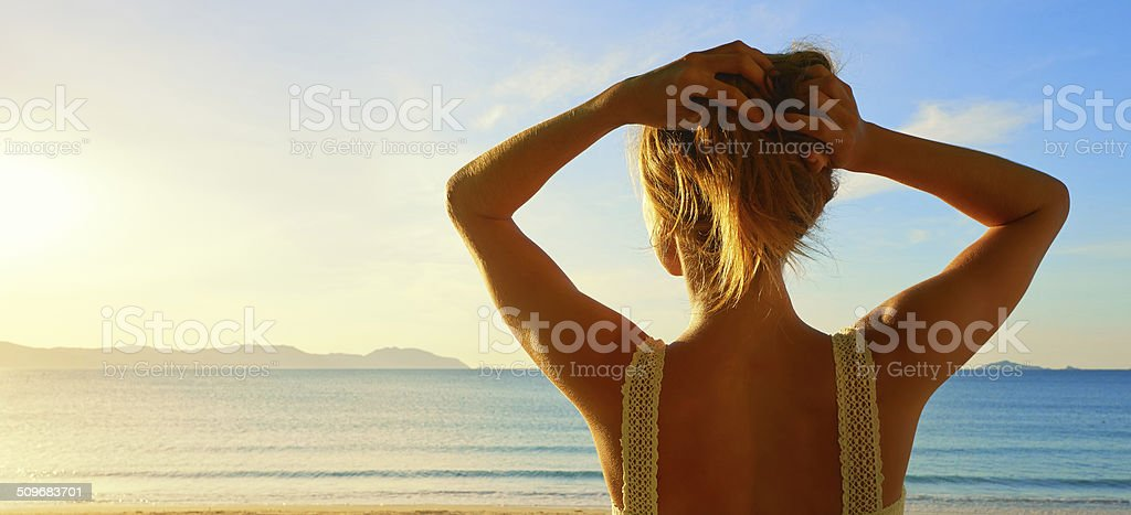 Back side view on wonderful young woman watching to sea stock photo