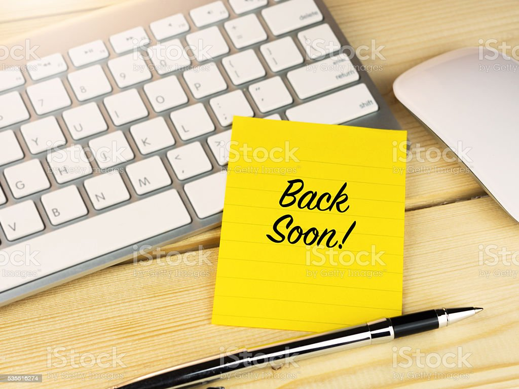 Back soon on sticky note on work table stock photo