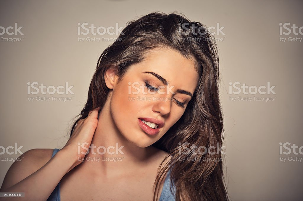 Back spine disease. Tired woman massaging her painful neck stock photo